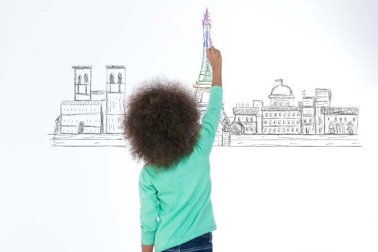 little girl drawing paris on a white wall